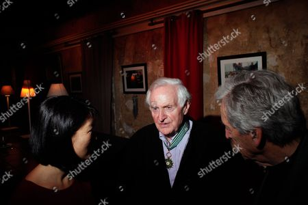 British director John Boorman, center, talks with French Culture minister Fleur Pellerin, left, and French director Costa Gavras, right, after being awarded the medal of commandeur de l'Ordre des Arts et Lettres, in Paris