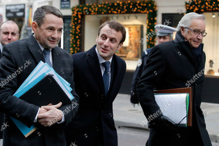 French Economy Minister Emmanuel Macron, center, Deputy minister for Government Reform Thierry Mandon, left, and Labor Minister Francois Rebsamen, right, walk with government members toward the Elysee Palace to attend the first cabinet meeting of the year, in Paris, . Valls and his ministers were gathered at the Interior ministry for the traditional New Year breakfast
