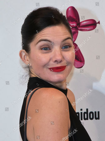 Stock Photo of French actress Delphine Chaneac, poses during a photocall at Georges Pompidou museum in Paris, . Fashion house H&M launched a new leather hand bag in collaboration with American artist Jeff Koons, which features a printed design of his famous sculpture Balloon Dog (Magenta), 1994
