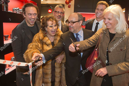 Stock Photo of From left, Swiss actor and director Vincent Perez, Italian actress Claudia Cardinale, Andreas Kaufmann, owner and CEO of Leica Camera AG and assistant major of the Paris' 8th district Erika Duverger cut the ribbon during the opening of a Leica concept shop in Paris, . The first 35mm film Leica prototypes were built by Oskar Barnack at Ernst Leitz Optische Werke, Wetzlar, in 1913