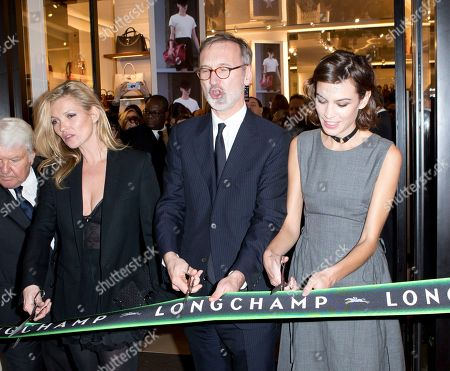British model Kate Moss holding scissors, left, Jean Cassegrain owner of Longchamp, center and British model Alexa Chung cut the ribbon at the opening of the Longchamp store in Paris, France
