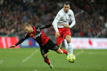 Paris Saint Germain's forward Zlatan Ibrahimovic of Sweden challenges for the ball with Guingamp's defender Lars Jacobsen during their League One soccer match, in Guingamp, western France, Sunday, Dec. 14, 2014
