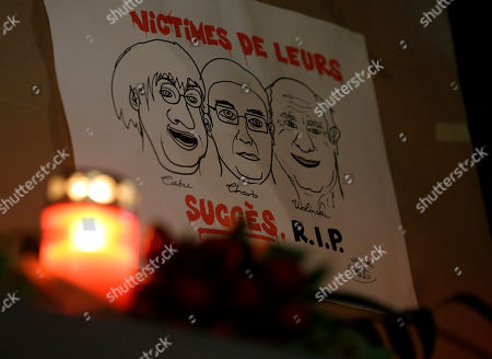 """A drawing depicting cartoonist Jean Cabut, left, Charlie Hebdo editor Stephane Charbonnier, center, and cartoonist Georges Wolinski, all three of whom were killed when masked gunmen stormed the Paris offices of a weekly newspaper Charlie Hebdo and reading in French, """"Victims of their success, R.I.P"""", is placed outside the French Embassy as people gather to express solidarity with victims of the attack in Berlin, Germany, . Three masked gunmen shouting """"Allahu akbar!"""" stormed the Paris offices of a satirical newspaper Wednesday, killing 12 people, including its editor, before escaping in a car. It was France's deadliest postwar terrorist attack"""