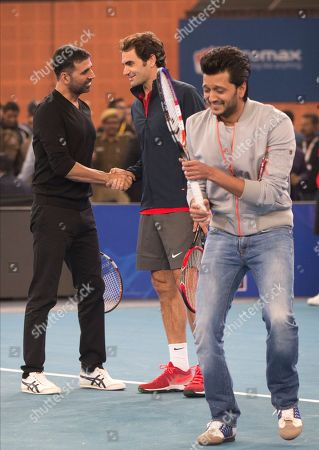 Micromax Indian Aces player Roger Federer, shakes hands with Indian Bollywood actor Akshay Kumar, left, as actor Ritesh Deshmukh passes by during a match on the sidelines of the International Premier Tennis League, in New Delhi, India