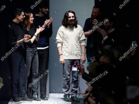 Stock Image of Italian Creative Director Alessandro Michele, center, acknowledges the applause of the audience after presenting Gucci men's Fall-Winter 2015-2016 collection, part of the Milan Fashion Week, unveiled in Milan, Italy. The Gucci fashion house has named Alessandro Michele as creative director for all the brands, succeeding Frida Giannini. Michele, who was Giannini's right-hand man, led the redesign of the entire menswear line for next autumn and winter, presented Monday during Milan Fashion Week, in just five days after Giannini left Gucci earlier than anticipated. The first collection under his name will be the women's ready-to-wear for next autumn and winter, to be shown Feb. 25. Michele, 42, joined Gucci in 2002, becoming associate to the creative director in May 2011. He added the role of creative director of the Richard Ginori porcelain brand, owned by Gucci, last September. He previously worked as a senior accessories designer at Fendi and studied at the Accademia di Costume e di Moda in Rome