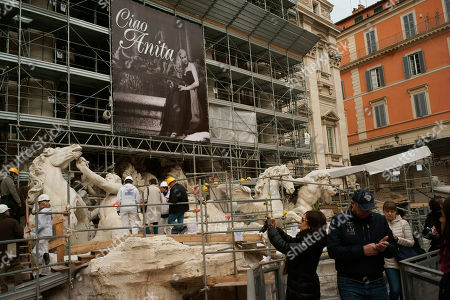 """A giant poster reading """"Ciao Anita"""" and featuring the Swedish-born actress Anita Ekberg in """"La Dolce Vita"""" is displayed on the facade of the Trevi fountain in Rome, . Ekberg, the sex-symbol of the 1950s and '60s who was immortalized bathing in the Trevi fountain in """"La Dolce Vita,"""" has died Sunday, Jan. 11, 2015. She was 83. Ekberg had long lived in Italy, the country that gave her worldwide fame thanks to the iconic dip opposite Marcello Mastroianni. The scene where the blond bombshell, clad in a black dress, her arms wide open, calls out """"Marcello"""" remains one of the most famous images in film history"""