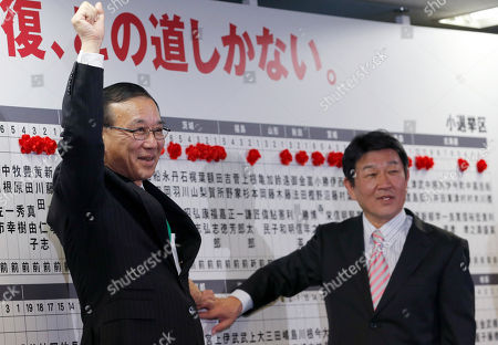 Sadakazu Tanigaki, Toshimitsu Moteg Liberal Democratic Party's Secretary General Sadakazu Tanigaki, left, and the party's Election Strategy Committee chairman Toshimitsu Motegi smile as they place a red rosette on the name of their party's winning candidate during ballot counting for the lower house election at the party headquarters in Tokyo, . Japanese Prime Minister Shinzo Abe's ruling party was headed for a landslide victory in lower house elections Sunday, according to projections released soon after polls closed