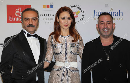 Olga Kurylenko, Yilmaz Erdogan Actress Olga Kurylenko, center, poses with Turkish actor Yilmaz Erdogan, left, on the red carpet at the Water Diviner screening as part of the Dubai International Film Festival in Dubai, United Arab Emirates