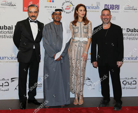Olga Kurylenko, Yilmaz Erdogan, Abdulhamid Juma Actress Olga Kurylenko, 2nd right, poses with Turkish actor Yilmaz Erdogan, 1st left, and Abdulhamid Juma, chairman of the Dubai International Film Festival, on the red carpet at the Water Diviner screening as part of the film festival in Dubai, United Arab Emirates
