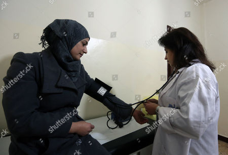 Stock Photo of Hoda Barakat, right, a registered midwife, takes the blood pressure of Syrian Manal Allan, 24, at a natal clinic in Beirut, Lebanon. Nearly 30,000 Syrian children born as refugees in Lebanon are in a legal limbo, not registered with any government, exposing them to the risk of a life of statelessness deprived of basic rights