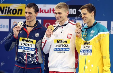 Winner Radoslaw Kawecki of Poland, left, second placed Tyler Clary of the USA, left, and third placed Mitchell James Larkin of Australia celebrate on the podium after the men's 200m backstroke event at the 12th FINA Short Course World Swimming Championships at Hamad Aquatic Centre in Doha on
