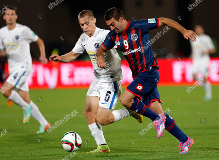 Auckland City FC's Tim Payne, center, is dribbled by San Lorenzo's Martin Cauteruccio during the semi final soccer match between Auckland City FC and San Lorenzo at the Club World Cup soccer tournament in Marrakech, Morocco