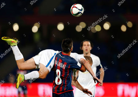 San Lorenzo's Enzo Kalinski looks at the ball while Auckland City FC's John Irving falls down during the semi final soccer match between Auckland City FC and San Lorenzo at the Club World Cup soccer tournament in Marrakech, Morocco