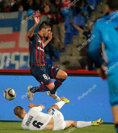 San Lorenzo's Enzo Kalinski jumps over Auckland City FC's John Irving during the semi final soccer match between Auckland City FC and San Lorenzo at the Club World Cup soccer tournament in Marrakech, Morocco