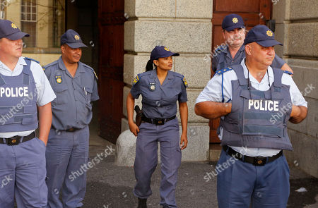 South African Police provide security as they await the arrival of Shrien Dwani at the high court in Cape Town, South Africa, . British man Shrien Dwani accused of killing his wife Anni while they were on honeymoon in Cape Town was acquitted of murder on Monday after a South African judge concluded that the prosecution's case did not have sufficient evidence. Shrien Dewani promptly descended stairs leading out of the courtroom following the not guilty ruling by Cape Town High Court Judge Jeanette Traverso