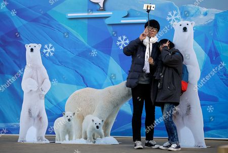 South Korean students Kim Gun-ho, left, poses with his friend Lee So-yeon for a selfie using a selfie stick near Seoul City Hall at Seoul Plaza in Seoul, South Korea, . Selfie sticks have become popular among tourists because you don't have to ask strangers to take your picture, and you can capture a wide view in a selfie without showing your arm