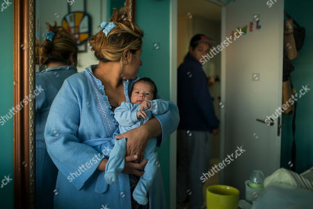 Cecilia Paredes, 43 years old, unemployed,left, and her baby, Dilan, remains in a room while her son Andres, right, and housing rights activists prepares to stop their eviction as police arrive to the building entrance in Madrid, Spain, . Paredes, her husband Wilson Ruilova, 35 years old also, unemployed both from Ecuador and her three children: Andres 16 years old, Miguel 7 years old, and Dilan 17 days old, live in an apartment of the City Hall Land Company (EMVS). They accumulated a debt as they could not afford to pay rent after she lost her job two years ago. The state company sold the apartment to an investor group who is now demanding their eviction. EMVS, a state company with an aim to give housing solutions for people in need, sold 1,860 state apartments to private investors, last year. The eviction was postponed
