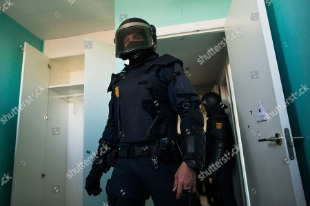 Riot police clear the apartment after they broke down the door during Cecilia Paredes and her family's eviction in Madrid, Spain, . Paredes, 43, and her unemployed electrician husband Wilson Ruilova, 35, both from Ecuador, have three children: Dilan, a baby born less than two months ago; Andres, 16, and Miguel, seven. They have been unable to pay their rent after she lost her job as an elderly care assistant two years ago. The government company that owned the apartment sold it last year to an investor group along with more than 1,800 other apartments built for the needy and the new owner sought the family's eviction