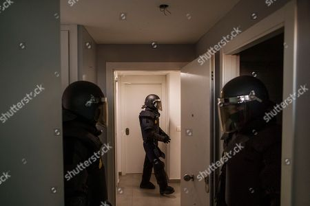 Stock Picture of Riot police stand guard as they clear the apartment after they broke down the door during Cecilia Paredes and her family's eviction in Madrid, Spain, . Paredes, 43, and her unemployed electrician husband Wilson Ruilova, 35, both from Ecuador, have three children: Dilan, a baby born less than two months ago; Andres, 16, and Miguel, seven. They have been unable to pay their rent after she lost her job as an elderly care assistant two years ago. The government company that owned the apartment sold it last year to an investor group along with more than 1,800 other apartments built for the needy and the new owner sought the family's eviction