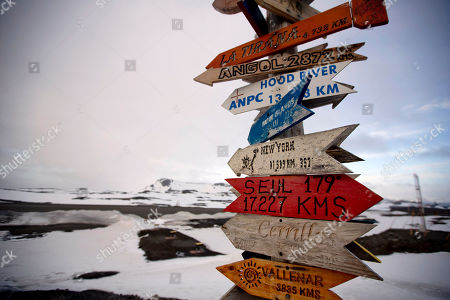 Wooden arrows show the distances to various cities near Chile's Escudero station on King George Island, Antarctica. Thousands of scientists come to Antarctica for research. There are also non-scientists, chefs, divers, mechanics, janitors and the priest of the worldís southernmost Eastern Orthodox Church on top of a rocky hill at the Russian Bellinghausen station
