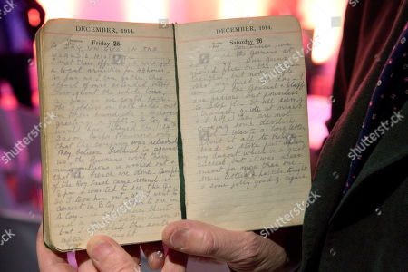 """On, Andrew Hamilton holds up the diary of his grandfather, World War I British Captain Robert Hamilton who served with the Royal Warwickshire Regiment, in Ploegsteert, Belgium. Many diaries and letters from World War I soldiers have come to light in the recent years which describe a lull in the fighting during Christmas 1914 along an approximately 500 mile stretch of front line from Belgium stretching to the Swiss border. The entry for Christmas Day 1914 reads, """"A day unique in the world's history. I met the officer and we arranged a local armistice for 48 hours. As far as I can gather, this effort of ours extended itself throughout the whole line. Soldiers on both sides met in their hundreds and exchanged greetings and gifts"""