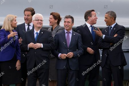 NATO Secretary General Anders Fogh Rasmussen, third right, stands with NATO leaders including U.S. President Barack Obama, right, British Prime Minister David Cameron, second right, Danish Prime Minister Helle Thorning-Schmidt, left, Dutch Prime Minister Mark Rutte, second left, Croatian President Ivo Josipovic, third left, and Slovenian Prime Minister Alenka Bratusek, fourth left, during a flypast at the NATO summit at the Celtic Manor Resort in Newport, Wales on