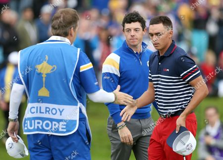 Europe's Rory McIlroy, center, looks on as Rickie Fowler of the US shakes hands with his caddie JP Fitzgerald after McIlroy wins the singles match on the 14th hole on the final day of the Ryder Cup golf tournament, at Gleneagles, Scotland