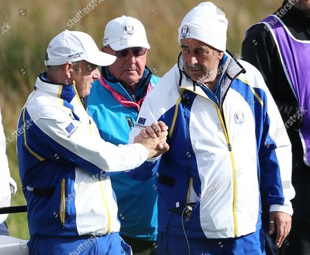 Europe team captain Paul McGinley, left, and vice captain Sam Torrance, right, shake hands on the 9th green during the foursomes match on the first day of the Ryder Cup golf tournament at Gleneagles, Scotland
