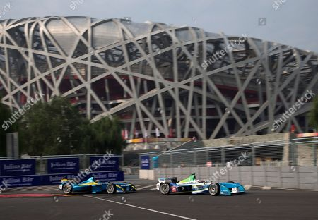 Jarno Trulli, Sebastian Buemi Trulli driver Jarno Trulli of Italy, right, is followed by E.dams Renault driver Sebastian Buemi of Switzerland in front of the iconic Bird's Nest National Stadium during a practice session for the Formula E all-electric auto race in Beijing