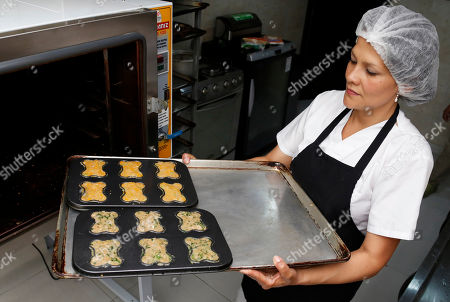 """Chef Alba Garcia shows a muffin tin with doggie snack dough at the """"Pet Gourmet Bakery & Boutique"""" in Bogota, Colombia, . The bakery's most popular products are the birthday cakes for dogs"""