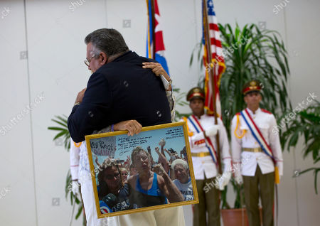 Diana Nyad, Jose Miguel Diaz Escrish U.S. endurance swimmer Diana Nyad, behind, embraces Jose Miguel Diaz Escrish, who runs the Hemingway Marina, as she holds a picture of herself taken the moment after she completed her swim from Cuba to Florida, in Havana, Cuba, . Cuba honored Nyad with the Order of Sporting Merit medal for being the first swimmer to make the crossing between Cuba and Florida without flippers or a shark cage for protection. Nyad made four previous attempts; first in 1978, and three times in 2011 and 2012. Nyad gave the photograph to Diaz as a gift