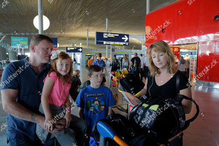 Stock Photo of Katie Ford of the U.S. right, checks her flight ticket as her husband Steve, left, her daughter Madie, second right, and her son Charlie look on at Paris Charles de Gaulle airport, in Roissy, near Paris, . Air France canceled at least half its flights around the world on Monday as pilots began a weeklong strike, highlighting the trouble Europe's flagship airlines face in keeping up with low-cost competitors. For Steve Ford, who with his family had planned to take Air France to Birmingham, England for a wedding, it's understandable: Pilots have tens of thousands of lives in their hands every day