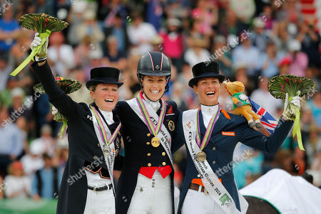 Charlotte Dujardin, Adelinde Cornelissen, Helen Langenhanenberg Medal winners from left, silver medalist gold medalist Helen Langenhanenberg of Germany, Charlotte Dujardin of Great Britain and Adelinde Cornelissen of the Netherlands, pose on the podium during the medal ceremony during freestyle Grand Prix individual dressage competition at the FEI World Equestrian Games, at Michel d'Ornano stadium in Caen, western France, . Charlotte Dujardin of Great Britain won on Valegro ahead of German Helen Langenhanenberg on Damon Hill and Dutch Adelinde Cornelissen on Jerich Parzival
