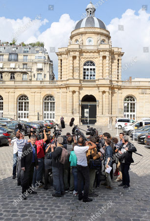 Reporters surround far-right National Front party newly elected senators David Rachline and Stephane Ravier, on their arrival at the Senate Assembly in Paris, . Conservatives won French Senate elections Sunday to take control of parliament's upper house, handing President Francois Hollande's Socialists a new setback. The National Front party also gained its first two Senate seats in the balloting