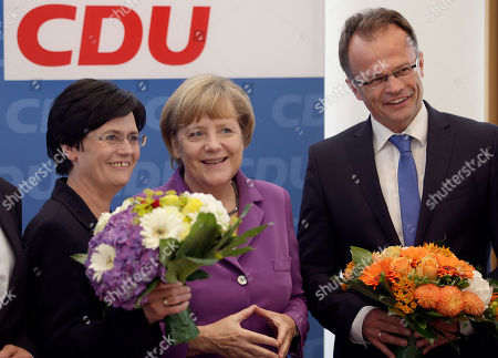 Christine Lieberknecht, Angela Merkel, Michael Schierack Chancellor and chairwoman of the German Christian Democrats, CDU, Angela Merkel, center, hands over a bunch of flowers to the CDU's top candidates for the state elections in Thuringia, Christine Lieberknecht, left, and in Brandenburg, Michael Schierack, right, at the beginning of the party's weekly executive committee meeting in Berlin, Germany, the day after the elections in these two German states