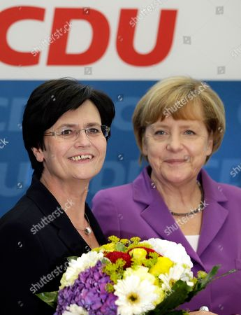 Stock Picture of Christine Lieberknecht, Angela Merkel Chancellor and chairwoman of the German Christian Democrats, CDU, Angela Merkel, center, hands over a bunch of flowers to the CDU's top candidate for the state elections in Thuringia, Christine Lieberknecht, left, at the beginning of the party's weekly executive committee meeting in Berlin, Germany, the day after the elections in the German states of Thuringia and Brandenburg