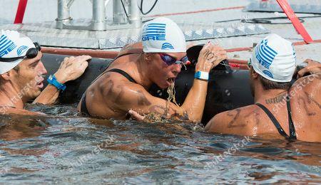 Antonios Fokaidis, Kalliopi Araouzou, Spyridon Gianniotis Greece's Kalliopi Araouzou center, is surrounded by Greece's Spyridon Gianniotis, left, and Greece's Antonios Fokaidis as she throws up after finishing second in the 5km Team Event of the open water swim competition at the LEN Swimming European Championships in Berlin, Germany
