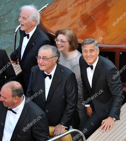 Actor George Clooney, right, looks up to photographers from a boat with, from left, his father Nick Clooney, Ramzi Alamuddin, father of her fiancee Amal Alamuddin, and his sister Adelia Zeidler, on their way to the Aman hotel ahead of his wedding in Venice, Italy