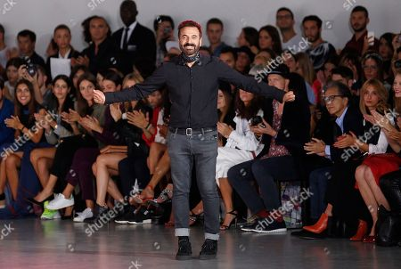 Fashion designer Ennio Capasa acknowledge the applause on the runway at the end of his Costume National women's spring-summer 2015 show, part of the Milan Fashion Week, unveiled in Milan, Italy