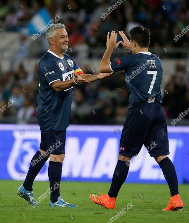 Roberto Baggio, left, congratulates Juan Iturbe after he scored during an inter-religious soccer match for peace, supported by Pope Francis to promote the dialogue and peace among different religions, at Rome's Olympic Stadium