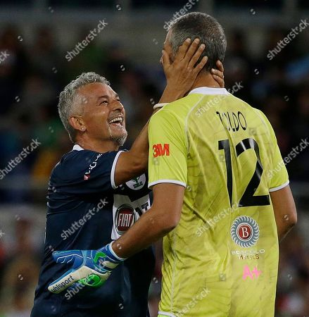 Roberto Baggio jokes with goalie Francesco Toldo after he scored a goal during an inter-religious soccer match for peace, supported by Pope Francis to promote the dialogue and peace among different religions, at Rome's Olympic Stadium