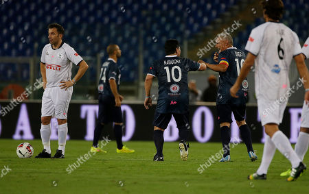 Argentine soccer legend Diego Armando Maradona, left, and Roberto Baggio celebrate after Juan Iturbe scored during an inter-religious soccer match for peace, supported by Pope Francis to promote the dialogue and peace among different religions, at Rome's Olympic Stadium