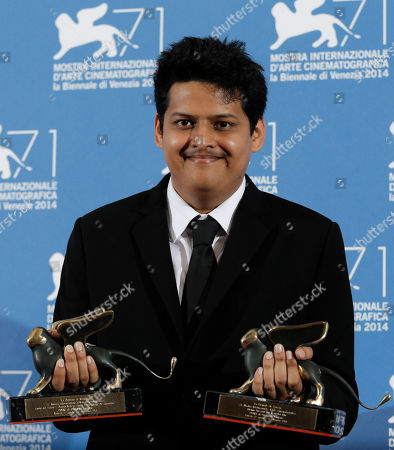 Chaitanya Tamhane Director Chaitanya Tamhane poses with the two prizes he won for best film in the Orizzonti section, and for best debut film with the movie Court, during a photo call at the 71th edition of the Venice Film Festival in Venice, Italy