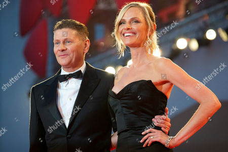 Director Andrew Niccol, left, and his partner Rachel Roberts pose for photographers as they arrive for the screening of Good Kill at the 71st edition of the Venice Film Festival in Venice, Italy