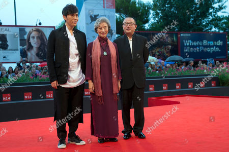 From left, actors Qin Hao and Lu Zhong, and director Wang Xiaoshuai arrive for the screening of the movie Red Amnesia, at the 71st edition of the Venice Film Festival in Venice, Italy