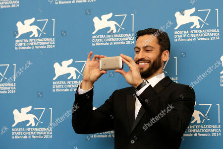 Adam Tsekhman Actor Adam Tsekhman takes a photograph during the photo call for the movie Tsili at the 71st edition of the Venice Film Festival in Venice, Italy