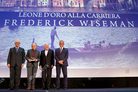 Frederick Wiseman, second from left, flanked by, from left, festival president Paolo Baratta, actor Michel Piccoli and festival director Alberto Barbera, holds the Lifetime Achievement Golden Lion he just received at the 71st edition of the Venice Film Festival in Venice, Italy
