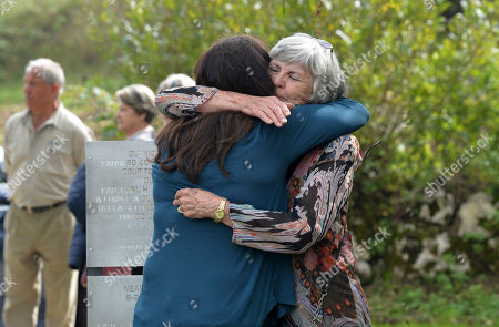 "Faye McBride, daughter of Isidore Ifshin a crew member who survived the crash, embraces Barbara Nash, right, the daughter of pilot Earl Remmel, during a ceremony to honor the memory two Americans at the controls of a B-25 Mitchell dubbed ""Maybe"" damaged during a bombing run near Trento during World War II, nearly 70 years after they died in the crash, at the crash site, near Santa Barbara, Italy, . Pilot Earl Remmel of Hooker, Oklahoma, and co-pilot Leslie Speer of Jeffersontown, Kentucky, kept the plane steady long enough for the other five crew members to bail out. The plane crashed into a mountain moments later"