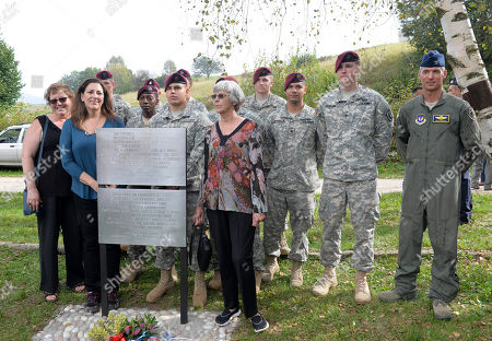 "From left, Deanne Ifhin-Batterman, her sister Faye McBride, daughter of Isidore Ifshin a crew member who survived the crash, and Barbara Nash, the daughter of pilot Earl Remmel, pose with soldiers from the Army's 173rd Airborne Brigade based in Aviano, Italy, after unveiling a memorial plaque bearing the pilots' names during a ceremony to honor the memory two Americans at the controls of a B-25 Mitchell dubbed ""Maybe"" damaged during a bombing run near Trento during World War II, nearly 70 years after they died in the crash, at the crash site, near Santa Barbara, Italy, . Pilot Earl Remmel of Hooker, Oklahoma, and co-pilot Leslie Speer of Jeffersontown, Kentucky, kept the plane steady long enough for the other five crew members to bail out. The plane crashed into a mountain moments later"