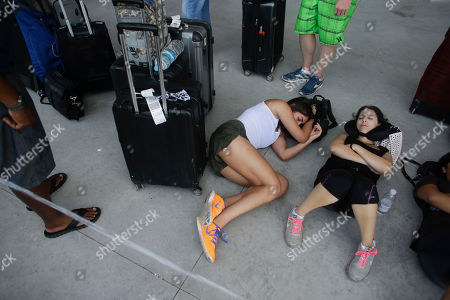 Nichole Yadidi, right, and her cousin Ashley Gharibian, second right, both from Los Angeles, California, sleep while waiting in line for a flight out of the airport in La Paz, Mexico, . Los Cabos' heavily damaged international airport was being powered by an emergency generator from the Federal Electricity Commission. Tourism Secretary Claudia Ruiz Massieu said 8,000 people, including tourists and locals anxious to leave, would be airlifted out on Thursday